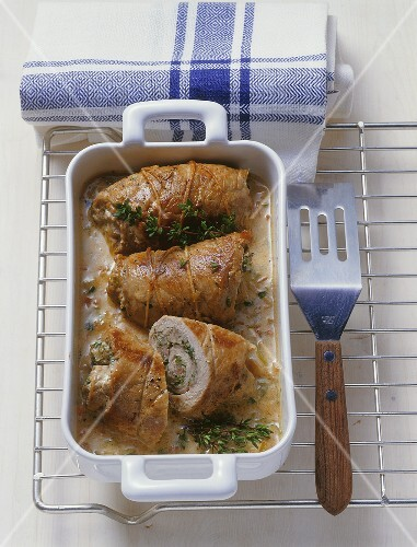Veal roulades with herbs & sausagemeat stuffing in roasting dish