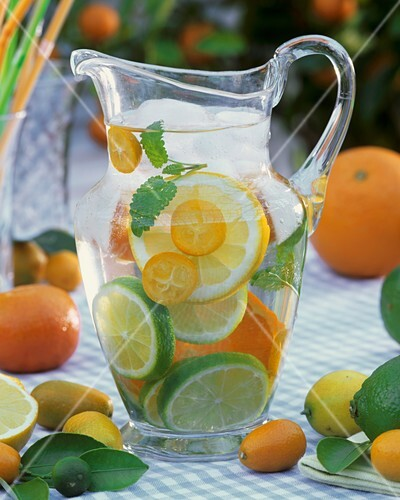 Jug of water with citrus fruit, lemon balm and ice cubes