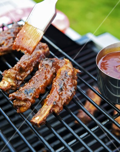 Brushing spare ribs on a grill with barbecue sauce