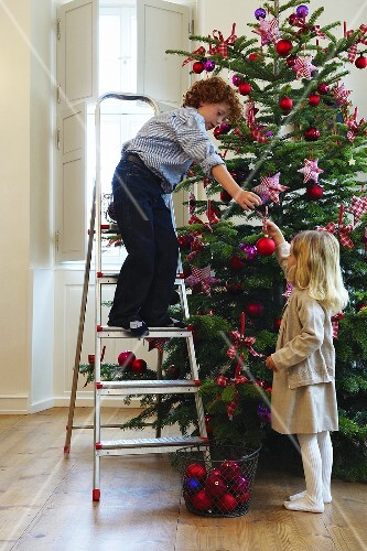 Two children decorating a Christmas tree