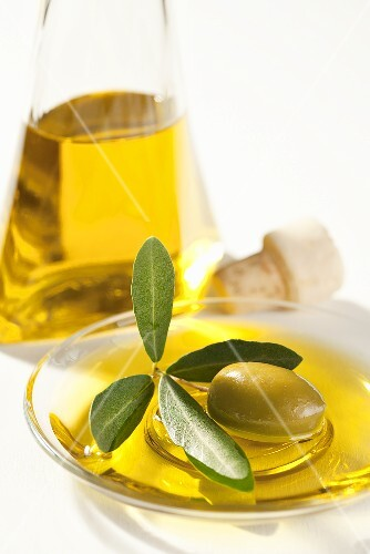 A bowl of olive oil with an olive