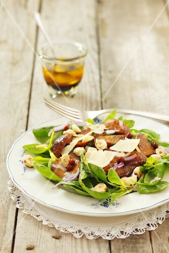 Spinach salad with fried mushrooms, Parmesan cheese and hazelnuts