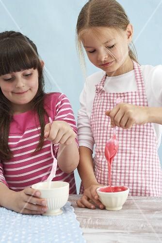 Two girls preparing icing sugar