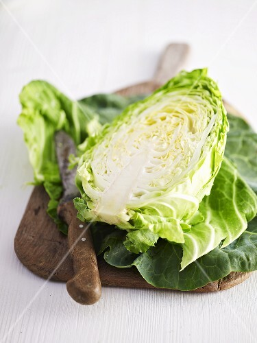 Half a pointed cabbage on a chopping board with a knife