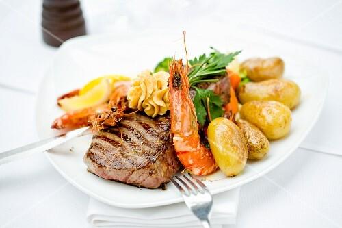 Rump steak with king prawns and potatoes