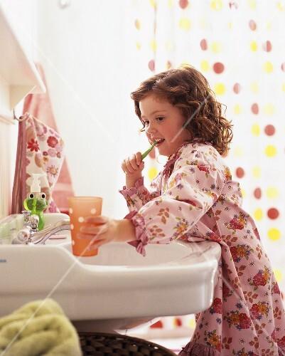 Little girl in bathrobe brushing her teeth