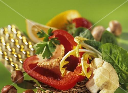Image symbolising vitamins: vitamin capsules, vegetables, nuts