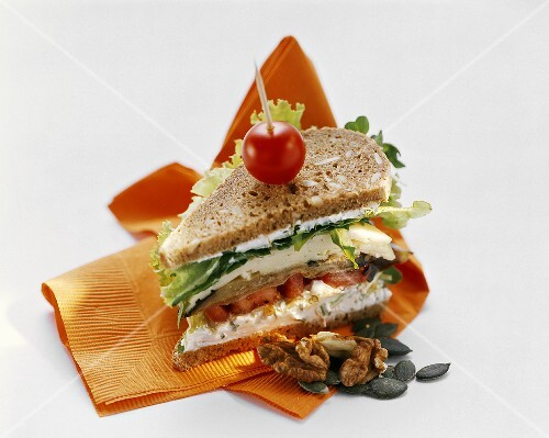 Wholemeal sandwich with herb quark, lettuce, cheese and nuts