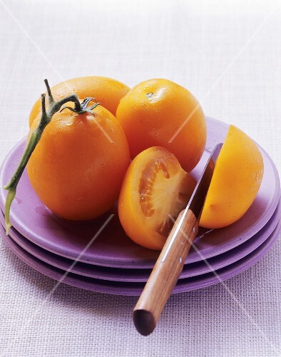 Whole and halved yellow tomatoes on plate
