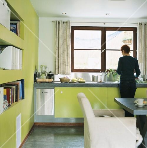 Frau beim Abwasch in Küche mit grünen Schrankfronten
