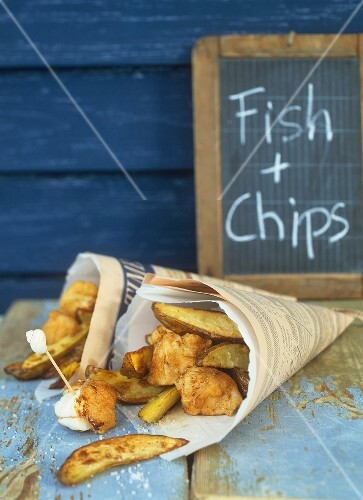 Fish and chips in newspaper, blackboard behind