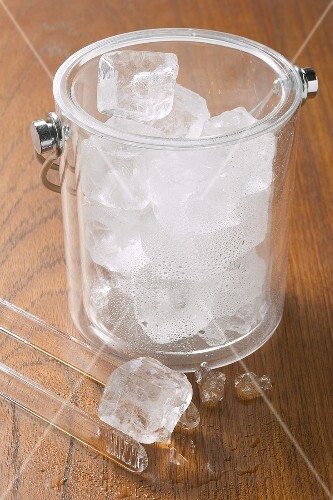 Ice cube with tongs and champagne bucket full of ice cubes