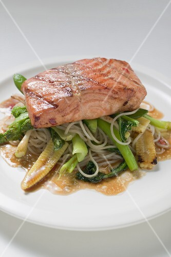 A fried salmon fillet on mie noodles and vegetables