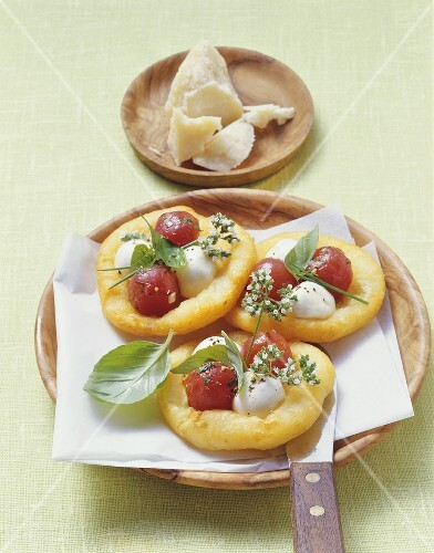 Small potato dough pizzas topped with tomatoes & mozzarella