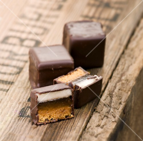 Dominosteine (chocolate covered sweets with marzipan and gingerbread) whole and halved on a wooden crate