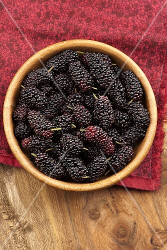 A wooden bowl of mulberries, seen from above