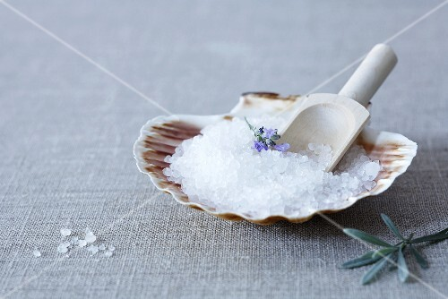 Sea salt in a scallop shell with a wooden scoop and lavender