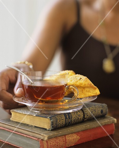 Woman putting a cup of tea and scones on a pile of books