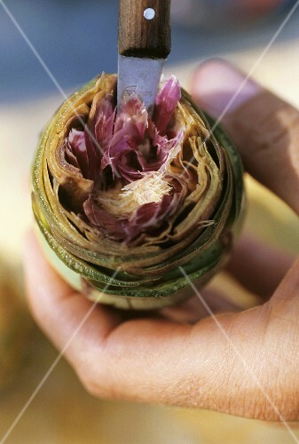 Hollowing out an artichoke with a knife