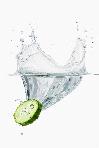 A slice of cucumber falling into water