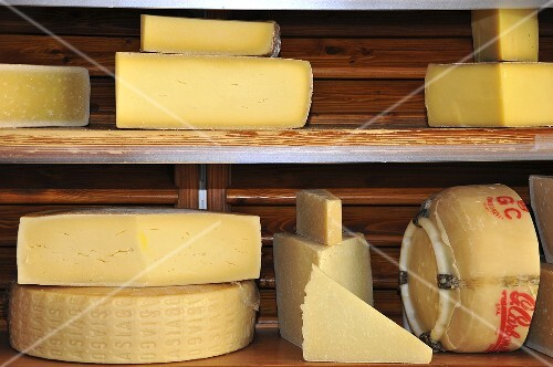 Parmesan and Provolone on a wooden shelf