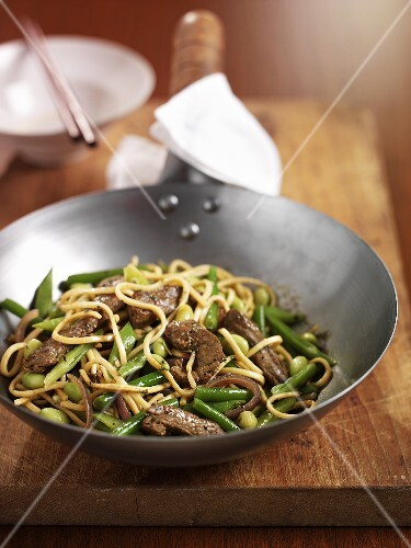Noodles with beef and green beans in wok