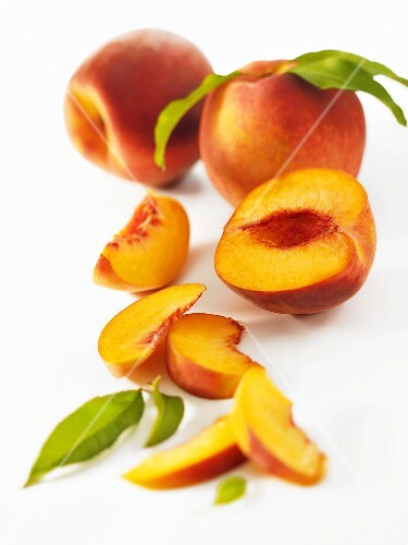 A partly-sliced peach, two whole peaches in background