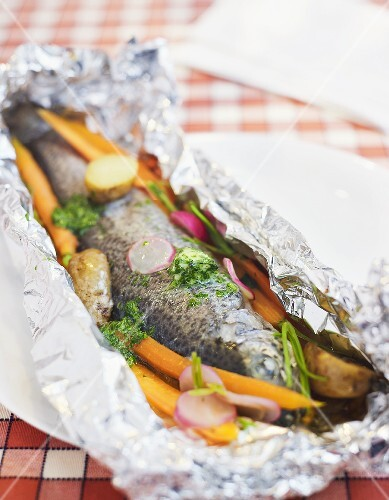 Grilled trout and vegetables in aluminium foil