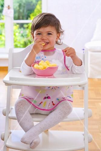 Little girl eating corn puffs