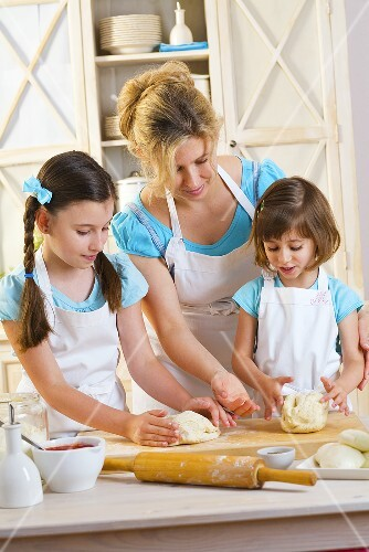 Mother and two daughters kneading pizza dough