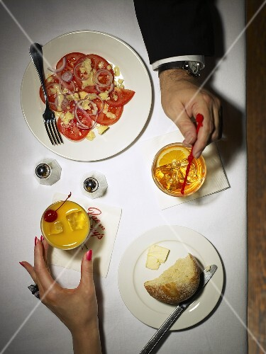 Man's and woman's hands on table with drinks and appetiser