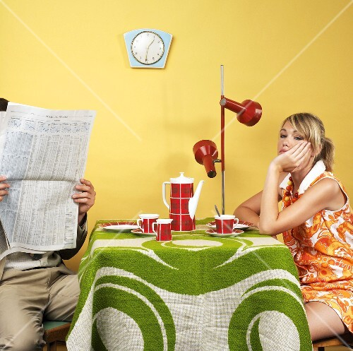 Young couple with coffee and newspaper