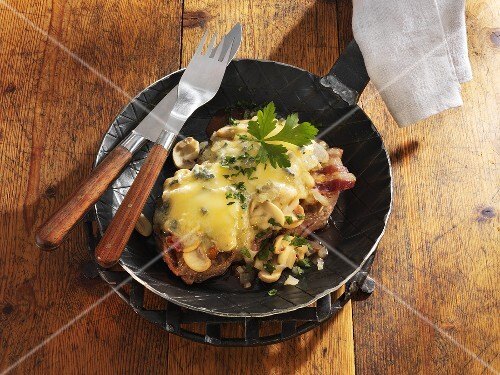 Steak with blue cheese, bacon and mushrooms in frying pan