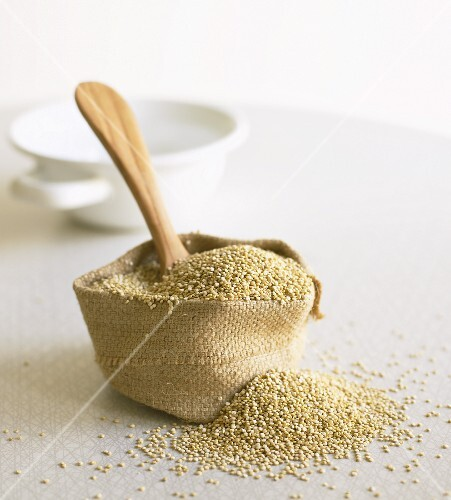 Quinoa in small sack with wooden spoon