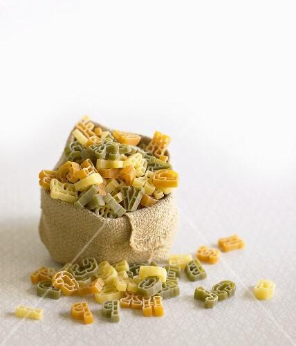 Coloured alphabet pasta in a small sack