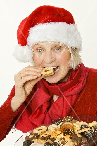 Elderly lady in Father Christmas hat eating a biscuit