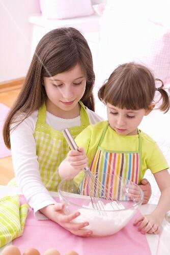 Two girls whisking egg white