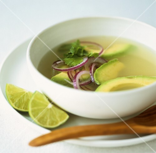Avocado soup with lime wedges and coriander leaves