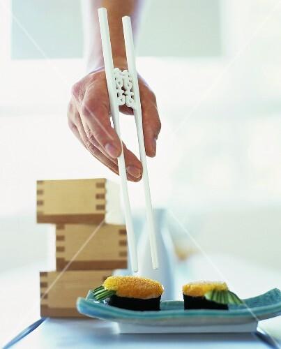 Sushi mit Essstäbchen greifen
