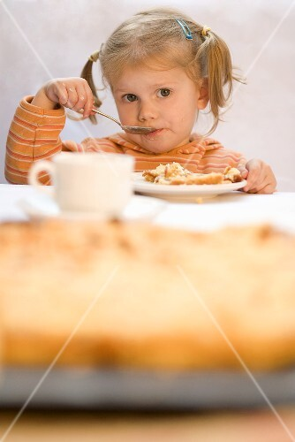 A little girl eating quince cake
