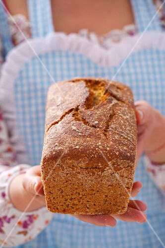 A woman in an apron holding a freshly baked loaf of bread