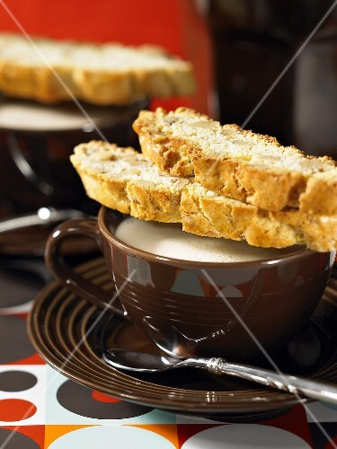 Walnut biscotti on a cappuccino cup