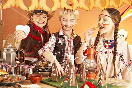 Three children dressed as cowboys and Indians at a party buffet