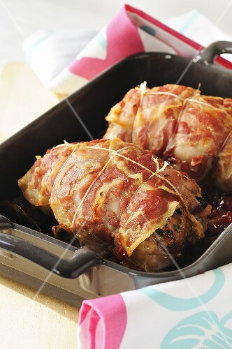 Roast rabbit wrapped in bacon with cranberries