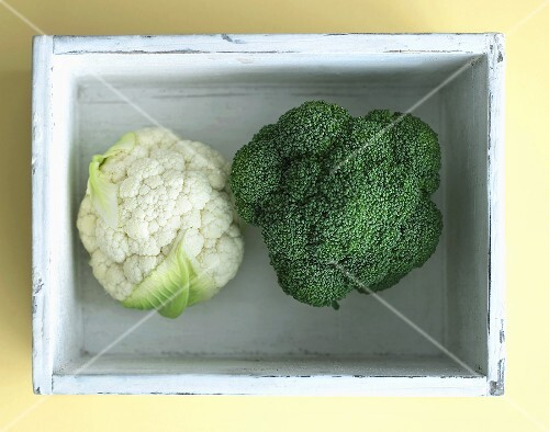 Cauliflower and broccoli in a wooden crate, seen from above