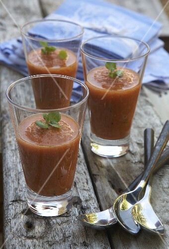 Three glasses of gazpacho on a wooden table
