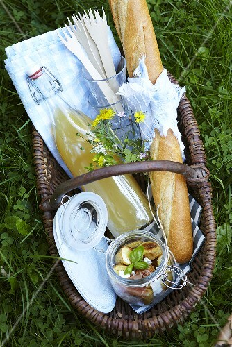 A picnic basket filled with juice, baguette and potato salad