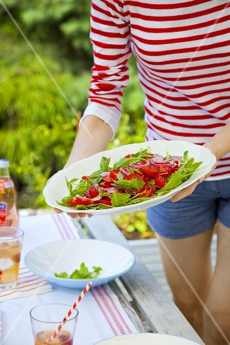 A girl holding a plate with a tomato and rocket salad