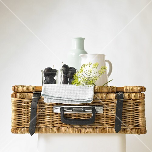 A picnic basket with plums, dill flowers and a porcelain jug