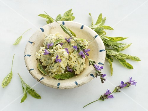 A bowl of sage butter, sage and sage flowers